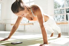 Η φίλαθλη γυναίκα ηλιακού εγκαύματος που κάνει το ώθηση-UPS στο χαλί ικανότητας και που χρησιμοποιεί το smartphone για τις αριθμή στοκ εικόνα