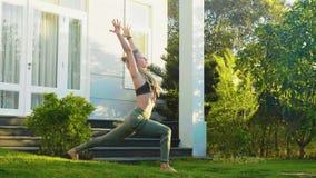 Η φίλαθλη γυναίκα κάνει την άσκηση πρακτικής γιόγκας στο κατώφλι του σπιτιού της φιλμ μικρού μήκους