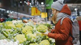 Η φίλαθλη κυρία της Νίκαιας επιλέγει το μπρόκολο σε μια στάση με τα λαχανικά στην υπεραγορά απόθεμα βίντεο