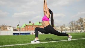 Η φίλαθλη νέα ασιατική γυναίκα τεντώνει στο στάδιο Αθλητισμός workout υπαίθρια απόθεμα βίντεο