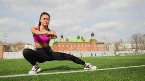 Η φίλαθλη νέα ασιατική γυναίκα τεντώνει στο στάδιο Αθλητισμός workout υπαίθρια φιλμ μικρού μήκους