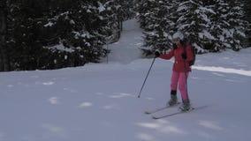 Η φίλαθλη νέα γυναίκα κάνει σκι κάτω από την κλίση στα βουνά των Άλπεων φιλμ μικρού μήκους