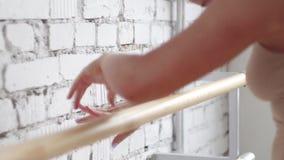 Η φίλαθλη ξανθή γυναίκα στο leotard κάνει τις ασκήσεις μπαλέτου στην μπάρα στο ελαφρύ δωμάτιο απόθεμα βίντεο