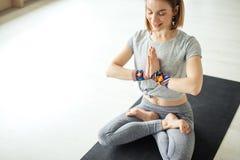 Η φίλαθλη συνεδρίαση γυναικών cross-legged στο λωτό θέτει στο φωτεινό δωμάτιο Στοκ Εικόνες