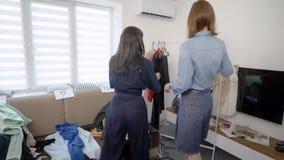 Η φίλη δύο γυναικών αποσυνθέτει την ντουλάπα Τα κορίτσια προσπαθούν στα διαφορετικά ενδύματα και αποφασίζουν πώς να ντύσουν επάνω απόθεμα βίντεο