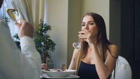 Η φίλη και ο φίλος τα γυαλιά, πίνουν τη σαμπάνια και μιλούν κατά τη ρομαντική ημερομηνία στο αριστοκρατικό εστιατόριο απόθεμα βίντεο