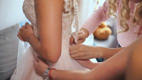 Η φίλη νυφών ` s βοηθά το φόρεμα νυφών επάνω το γαμήλιο φόρεμά της φιλμ μικρού μήκους