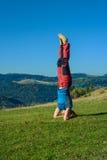 Η φίλαθλη γυναίκα ασκεί τη γιόγκα στα βουνά φθινοπώρου Στοκ Φωτογραφίες