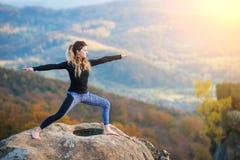 Η φίλαθλη κατάλληλη γυναίκα ασκεί τη γιόγκα στην κορυφή του βουνού Στοκ Φωτογραφία