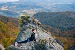 Η φίλαθλη κατάλληλη γυναίκα ασκεί τη γιόγκα στην κορυφή του βουνού στοκ φωτογραφίες