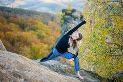 Η φίλαθλη κατάλληλη γυναίκα ασκεί τη γιόγκα στην κορυφή του βουνού Στοκ Εικόνες