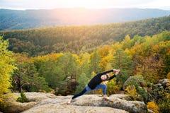 Η φίλαθλη κατάλληλη γυναίκα ασκεί τη γιόγκα στην κορυφή του βουνού Στοκ φωτογραφία με δικαίωμα ελεύθερης χρήσης