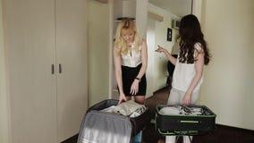 Η φίλη κοριτσιών συλλέγει τα πράγματα στις βαλίτσες φιλμ μικρού μήκους