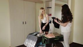 Η φίλη κοριτσιών συλλέγει τις βαλίτσες για τις διακοπές απόθεμα βίντεο