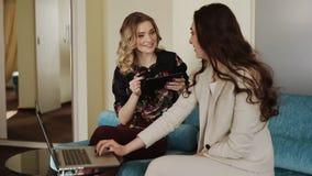 Η φίλη με ένα lap-top και planshetome επικοινωνεί στα κοινωνικά δίκτυα απόθεμα βίντεο