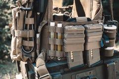 Η φανέλλα στρατού με walkie-talkie, χρέωσε τα περιλαίμια, ζαλίζει τις χειροβομβίδες, φωτεινά ραβδιά στοκ εικόνες