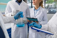 Η φιάλη εκμετάλλευσης χεριών επιστημόνων και η ομάδα ερευνητών κάνουν τις σημειώσεις της έρευνας στο εργαστήριο, επιστημονική ανά Στοκ Εικόνες