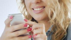 Η φιλική γυναίκα με ένα όμορφο χαμόγελο απολαμβάνει στενό έναν επάνω smartphone απόθεμα βίντεο