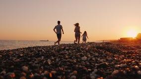 Η φιλική οικογένεια με ένα παιδί πηγαίνει μέσα για τον αθλητισμό, τρέξιμο μαζί στη γραμμή κυματωγών φιλμ μικρού μήκους