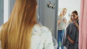 Η φιλική πωλήτρια βοηθά το θηλυκό πελάτη για να επιλέξει ένα παλτό Ο εύθυμος αγοραστής στέκεται στο δωμάτιο συναρμολογήσεων στο μ απόθεμα βίντεο