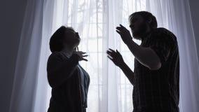 Η φιλονικία μιας νέας οικογένειας, ο σύζυγος κραυγάζει στη σύζυγό του, η έννοια σύγκρουσης, οικογενειακή βία, ένα παράθυρο απόθεμα βίντεο