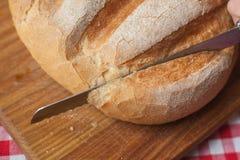 Η φλοιώδης φραντζόλα στη τοπ άποψη είναι σε έναν ξύλινο πίνακα και από το μαχαίρι στοκ φωτογραφία με δικαίωμα ελεύθερης χρήσης