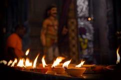 Η φλόγα των τελετουργικών ιερών κεριών πετρελαίου, στον οπαδό υποβάθρου πλησιάζει το άγαλμα Krishna στοκ φωτογραφίες με δικαίωμα ελεύθερης χρήσης