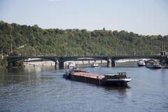 Η φορτηγίδα και Tugboat το φορτηγό πλοίο και ο ποταμός ταξιδεύουν τη ναυσιπλοΐα στον ποταμό Vltava κοντά στη γέφυρα του Charles Στοκ Φωτογραφία