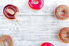 Η φράουλα και η σοκολάτα donuts επίπεδες βάζουν στο ξύλινο πρότυπο άποψης υποβάθρου τοπ Στοκ εικόνα με δικαίωμα ελεύθερης χρήσης