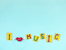 Η φράση: ` Ι μουσική ` αγάπης στις αποκόπτως επιστολές με τα ακουστικά, αγαπώ την έννοια μουσικής στοκ φωτογραφίες