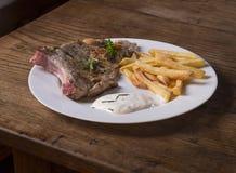Η φρέσκια γίνοντη ψημένη στη σχάρα μπριζόλα μπριζολών χοιρινού κρέατος με τις τηγανιτές πατάτες πελεκά πράσινο Στοκ Φωτογραφίες