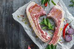 Η φρέσκια μέση χοιρινού κρέατος έκοψε έτοιμο να μαγειρεψει εξυπηρετημένος με το λογικό, κόκκινο κρεμμύδι, τα τσίλι και το κόκκινο Στοκ Φωτογραφίες
