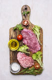 Η φρέσκια μπριζόλα χοιρινού κρέατος με τη σαλάτα, η ντομάτα, το έλαιο και το άλας σε μια κοπή επιβιβάζονται ξύλινο αγροτικό στενό Στοκ φωτογραφία με δικαίωμα ελεύθερης χρήσης