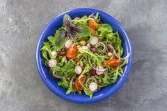 Η φρέσκια σαλάτα χορταριών με τα φυλλώδη πράσινα και nasturtium τα λουλούδια εξυπηρέτησε στο μπλε κεραμικό κύπελλο στο γκρι Στοκ Εικόνα