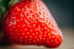 Η φρέσκια φράουλα σε ένα σκοτεινό ξύλινο υπόβαθρο, κλείνει επάνω της μεγάλης φράουλας στο ξύλο Στοκ Εικόνες