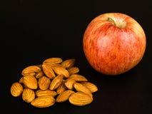 Η φρέσκια ώριμη Apple με μια χούφτα των ψημένων καρυδιών αμυγδάλων Στοκ εικόνα με δικαίωμα ελεύθερης χρήσης