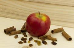 Η φρέσκια juicy Apple με την κανέλα στην ξύλινη επιτροπή με τον οργανικό χορτοφάγο σταφίδων στο ξύλινο υπόβαθρο Στοκ Φωτογραφίες