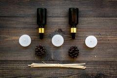 Η φροντίδα δέρματος και χαλαρώνει Καλλυντικά και aromatherapy έννοια Πετρέλαιο πεύκων στη σκοτεινή ξύλινη τοπ άποψη υποβάθρου Στοκ Φωτογραφία