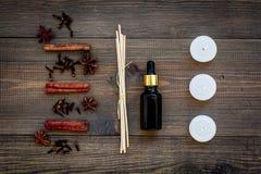Η φροντίδα δέρματος και χαλαρώνει Καλλυντικά και aromatherapy έννοια Πετρέλαιο κανέλας και κεριά στη σκοτεινή ξύλινη τοπ άποψη υπ Στοκ Εικόνες