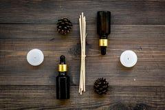 Η φροντίδα δέρματος και χαλαρώνει Καλλυντικά και aromatherapy έννοια Πετρέλαιο πεύκων στη σκοτεινή ξύλινη τοπ άποψη υποβάθρου Στοκ Εικόνες