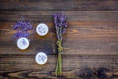 Η φροντίδα δέρματος και χαλαρώνει Καλλυντικά και aromatherapy έννοια Lavender spa άλας και κεριά στη σκοτεινή ξύλινη κορυφή υποβά Στοκ Εικόνες
