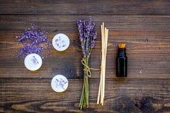 Η φροντίδα δέρματος και χαλαρώνει Καλλυντικά και aromatherapy έννοια Lavender SPA άλας και έλαιο στη σκοτεινή ξύλινη τοπ άποψη υπ Στοκ φωτογραφία με δικαίωμα ελεύθερης χρήσης