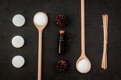 Η φροντίδα δέρματος και χαλαρώνει Καλλυντικά και aromatherapy έννοια Pine spa άλας, πετρέλαιο και pinecones στη μαύρη τοπ άποψη υ Στοκ φωτογραφία με δικαίωμα ελεύθερης χρήσης
