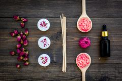Η φροντίδα δέρματος και χαλαρώνει Καλλυντικά και aromatherapy έννοια Rose spa άλας και έλαιο στη σκοτεινή ξύλινη τοπ άποψη υποβάθ Στοκ Εικόνα