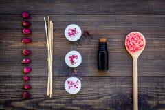 Η φροντίδα δέρματος και χαλαρώνει Καλλυντικά και aromatherapy έννοια Rose spa άλας και έλαιο στη σκοτεινή ξύλινη τοπ άποψη υποβάθ Στοκ φωτογραφία με δικαίωμα ελεύθερης χρήσης