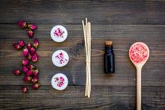 Η φροντίδα δέρματος και χαλαρώνει Καλλυντικά και aromatherapy έννοια Rose spa άλας και έλαιο στη σκοτεινή ξύλινη τοπ άποψη υποβάθ Στοκ Εικόνες