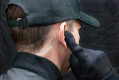 Η φρουρά ασφάλειας ακούει το ακουστικό, πέρα από τον ώμο Στοκ φωτογραφία με δικαίωμα ελεύθερης χρήσης