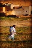 Η φτωχά muslin ηλικιωμένη κυρία και το παιδί περπατούν στο παλαιό παραδοσιακό Μαρόκο αραβικά Medina και χωριό στοκ φωτογραφία