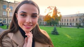Η φυσική καθαρή όμορφη καυκάσια γυναίκα κρατά τη κάμερα και κάνει τα καλλιτεχνικά πρόσωπα στεμένος υπαίθριος, όντας ευτυχώς φιλμ μικρού μήκους
