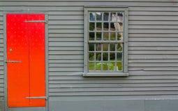 Η φωτεινή κόκκινη ξύλινη πόρτα με τη διακόσμηση και το πολλαπλάσιο καρφιών το παράθυρο στον τοίχο του αποικιακού κτηρίου Στοκ φωτογραφίες με δικαίωμα ελεύθερης χρήσης